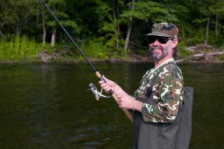 Joyful fisherman catches of salmon in the river. Stock Photo - 17798936