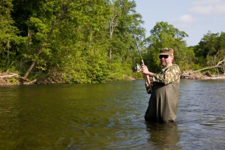 Fisherman pulls caught salmon. River. Stock Photo - 17798967
