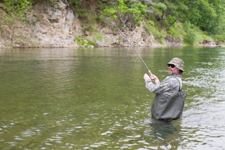 Fisherman catches of salmon in a mountain river. Stock Photo - 17798972
