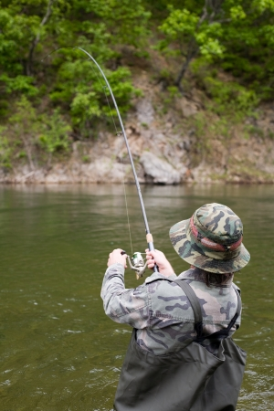Fisherman pulls caught salmon from the river. Stock Photo