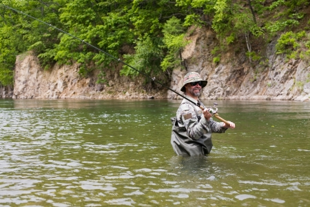 Fisherman catches of salmon in a mountain river. Stock Photo - 17798973