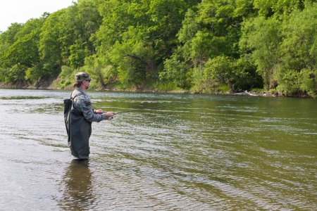 Fisherman catches of salmon in a mountain river. Stock Photo - 17799001