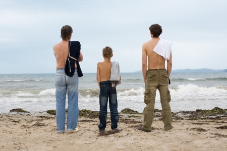 Father, son and grandson looking at the ocean. photo