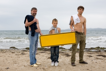 Men of different generations hold an empty banner on the beach. photo