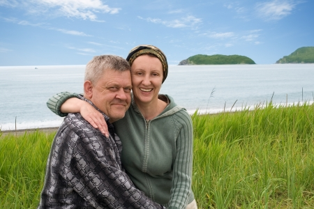 Happy middle aged couple outdoors by the sea. photo