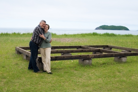 Happy middle aged couple in the construction of a house by the sea. photo