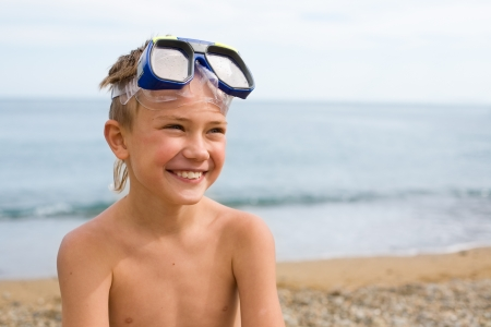 resting mask: Joyful boy on the beach in a mask for scuba diving.