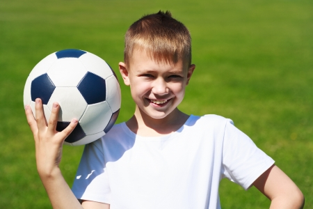 Boy with ball on the football field. photo