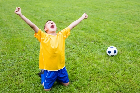 young cheering: Excited boy football player after goal scored