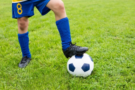 kids activities: Soccer ball with their feet boy on the football field
