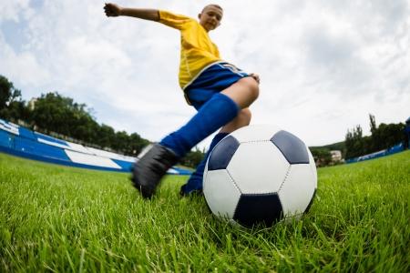 hits: Boy soccer player hits the ball on the football field  Fish-eye lens  Stock Photo