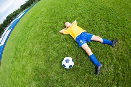 Dreaming boy soccer player lying on natural grass  Fish-eye lens  photo