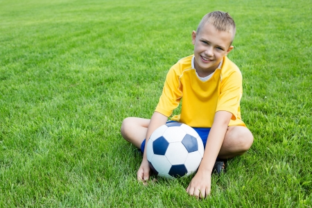 young boy feet: Boy soccer player with the ball is sitting on the football field  Stock Photo