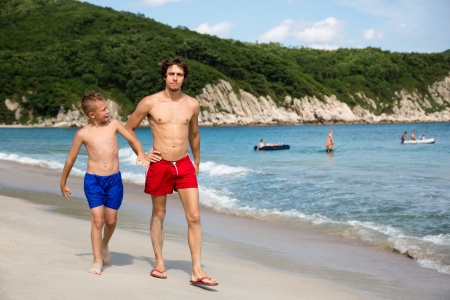 Senior and junior brothers walking along the sandy sea beach  photo