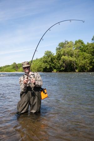 Joyful fisherman pulls caught salmon from the river. Фото со стока