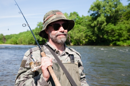 Portrait of a fisherman on a fishing trip on the river. Stock Photo - 22247386