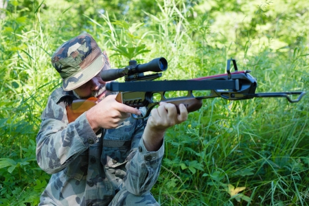 crossbow: Hunter shoots a crossbow in the woods. Stock Photo