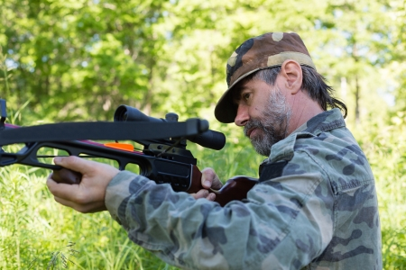 Hunter shoots a crossbow in the woods. photo