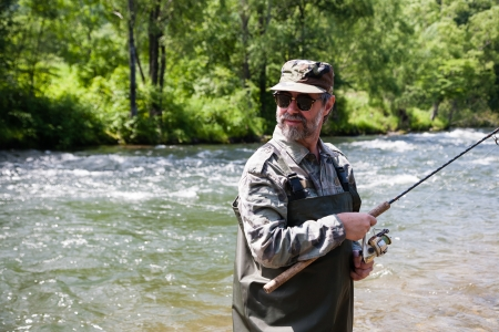 Fisherman catches of salmon in a mountain river. Stock Photo - 22371854
