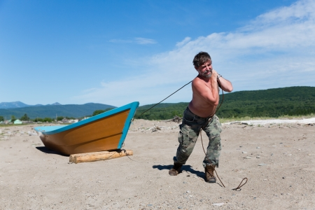 Fisherman pulls a heavy wooden boat out to sea. Humor.
