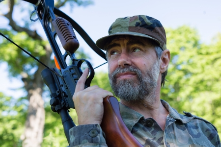 Hunter holding a crossbow in the woods. Stock Photo - 22403157