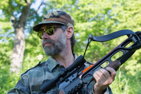 Hunter holding a crossbow while in the woods. photo