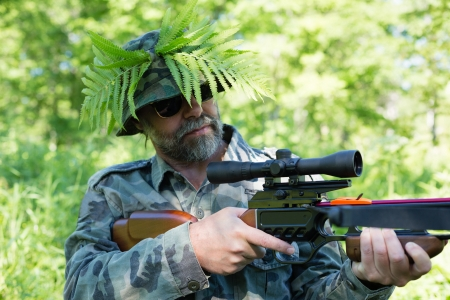 Hunter in camouflage aims a crossbow. Focus on the crossbow. photo