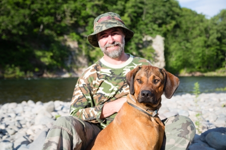 Traveler with a Rhodesian Ridgeback by the river. photo