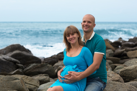 Happy pregnant woman and her husband on the sea coast  Stock Photo