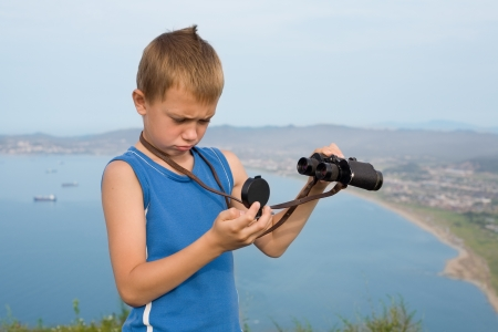 Boy hiker with binoculars looking at the compass on top of the mountain. photo