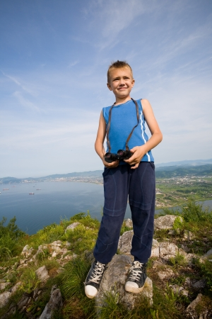 Boy hiker with binoculars standing on top of a mountain. photo