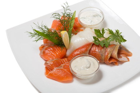 Cold appetizer of smoked halibut, salted trout, sockeye salmon salting cognac with lemon cream mushroom sauce. photo