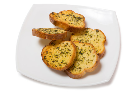drenched: Garlic croutons drenched with herb butter isolated on white.