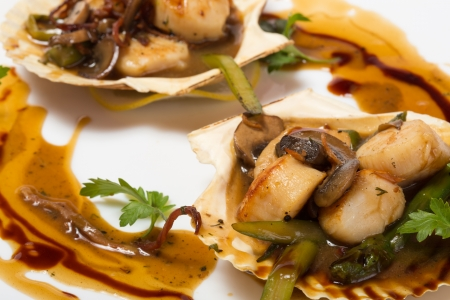 Hot starter of scallops with asparagus and mushrooms in the wings of the shells. photo