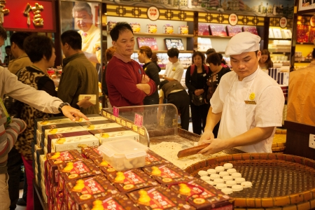 MACAU, CHINA - OCTOBER 31  Confectioner manufactures biscuits in candy store  Manufacture and sale of confectionery products is very popular business in Macau
