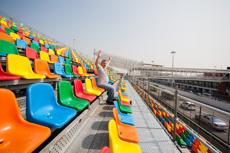 Screaming enthusiastic man with hands up in the seats for spectators, before the start of cars racing  Race takes place on the streets