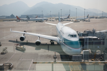 HONG KONG, CHINA - NOVEMBER 4, 2012: Preparing of airplane for flight in Hong Kong International Airport, photographed through glass.The one of the best airport in the annual passenger survey by Skytrax. Editorial