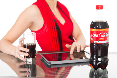 NAKHODKA, RUSSIA - JANUARY 18, 2014: Girl holding a glass of Coca-Cola on the table is a bottle of Coca-Cola, tablet pc. Coca-Cola is a very popular carbonated soft drink sold in stores, restaurants worldwide.