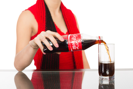 pours: NAKHODKA, RUSSIA - JANUARY 18, 2014: Young woman pours a Coca-Cola from a bottle into a glass. Coca-Cola is a carbonated soft drink sold in stores, restaurants, and vending machines worldwide. Editorial