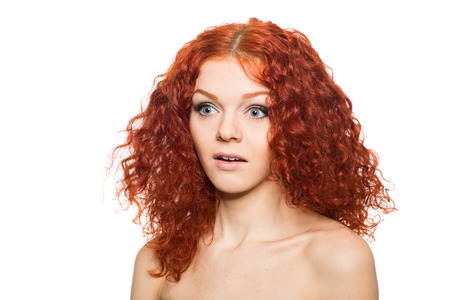 Surprised young woman with wavy red hair  photo