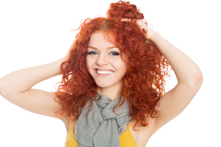 Joyful young girl with red hair holding his head in his hands  photo
