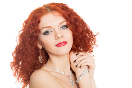 Smiling girl with curly red hair isolated on white   photo