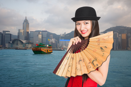 Beautiful girl on the background of Hong Kong with a fan.  photo