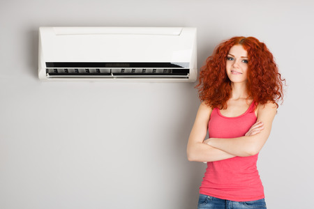 Beautiful red haired girl near an air conditioner. Stock Photo