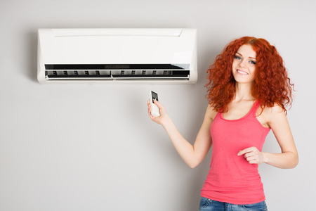 Smiling red haired girl holding a remote control air conditioner.