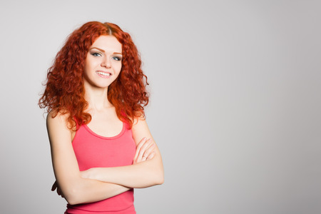 Smiling young woman with red hair on gray background wall. photo