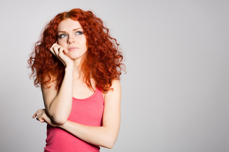 Portrait thinking red haired young woman on a background of gray wall. photo