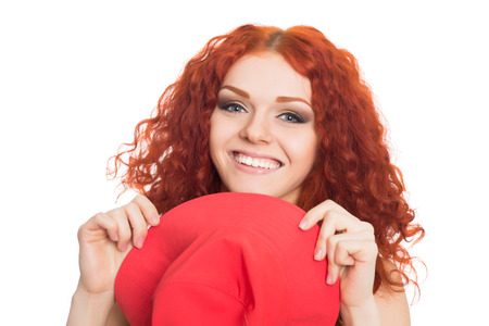 Happy red haired young woman holding hat  photo