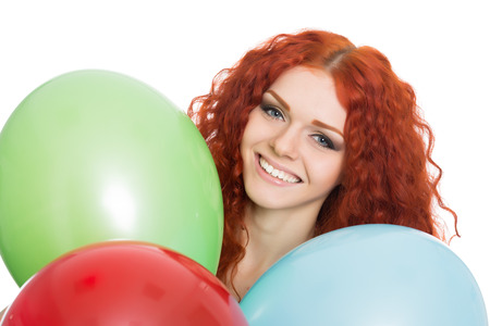 Happy red haired young woman holding colorful balloons.  photo