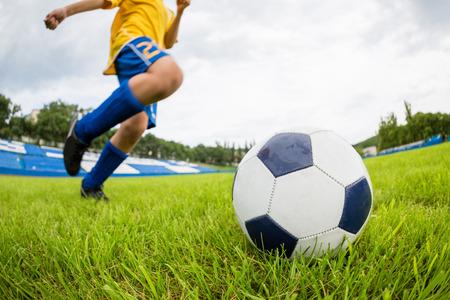 Jugador de fútbol del muchacho golpea el balón en el estadio de campo. Lente Ojo de Pez.